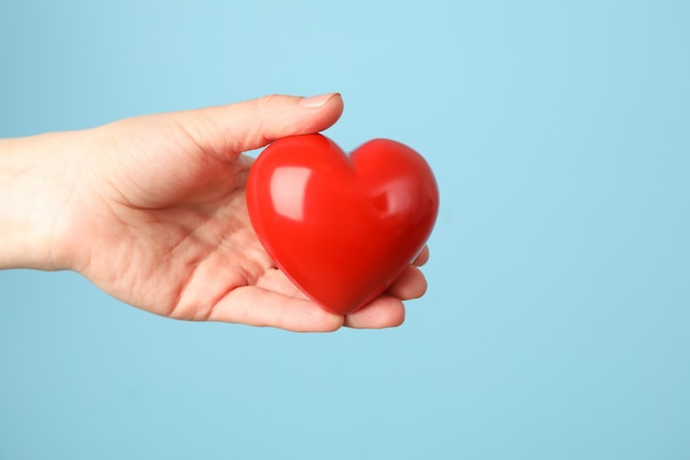 Female hand holds heart on blue space. health care, organ donation