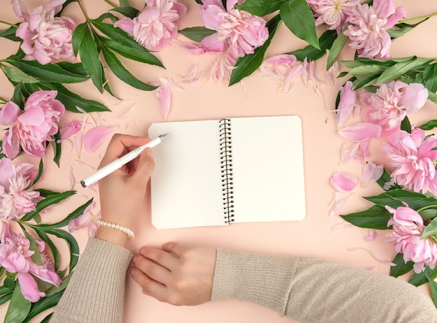 Female hand holds in her left hand a white pen over a spiral notebook with empty white pages