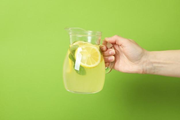 Женская рука держит кувшин с лимонадом на зеленом фоне