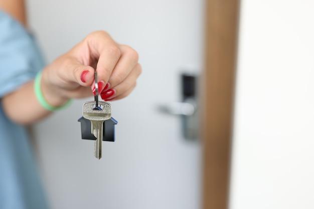 Женская рука держит ключ от инвестиций в дом и концепции ипотеки