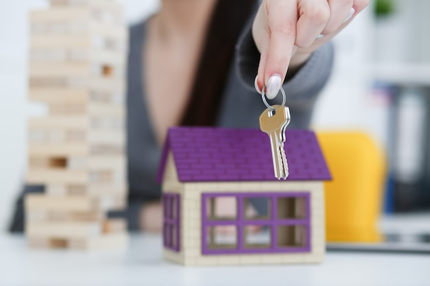 Female hand holds the key to the lock in the hand against the backdrop of the toy house sale purchase lease concept real estate services on the market.