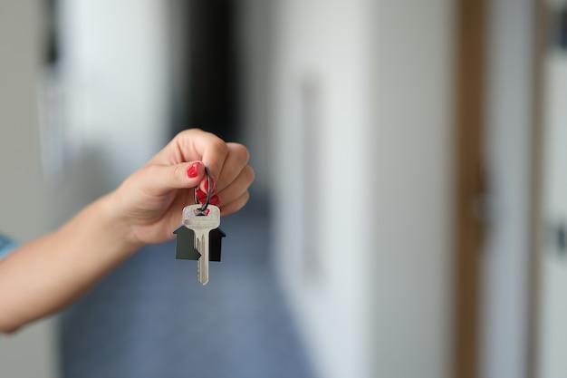 Женская рука держит ключ от квартиры крупным планом