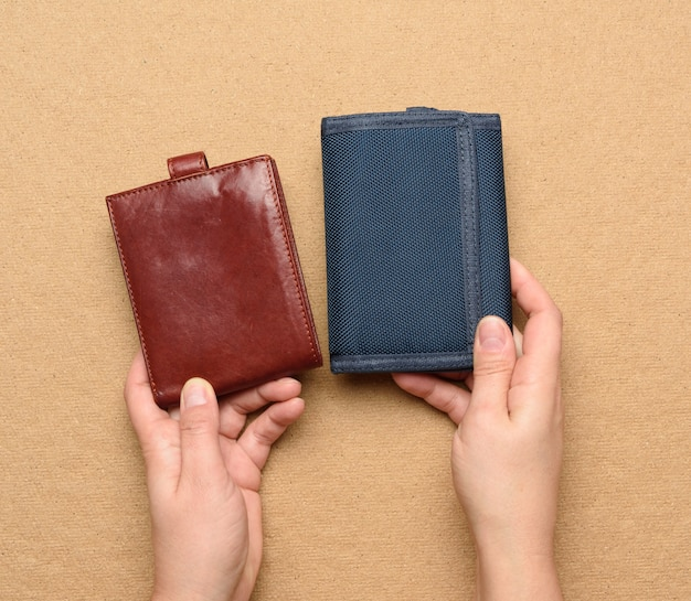 Female hand holds leather and blue textile wallet, close up