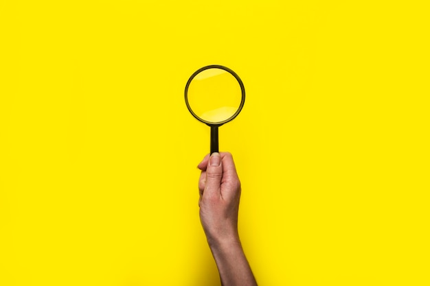 Female hand holds a magnifying glass loupe on a yellow surface.
