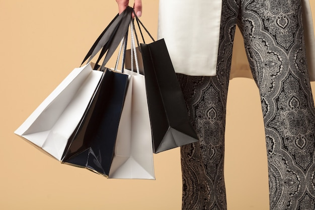 Female hand holds many shopping bags isolated on beige background