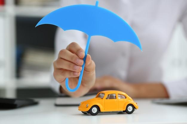 The female hand holds a miniature umbrella