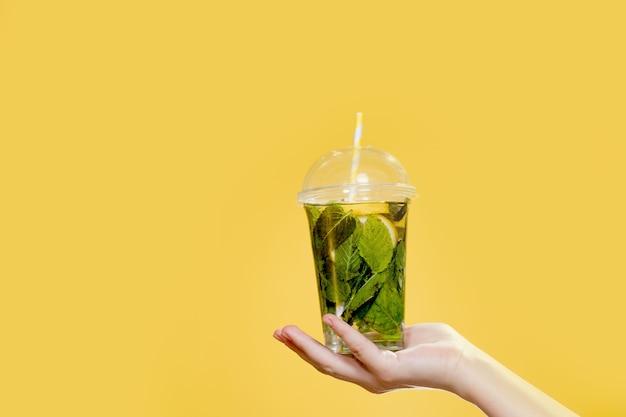 Женская рука держит напиток мохито в пластиковом стаканчике на желтом фоне