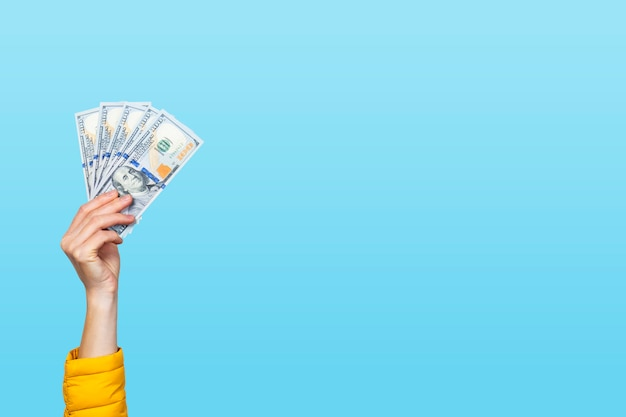 Female hand holds money, dollar banknotes on a blue background