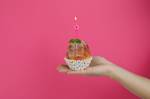 Female hand holds muffin with one candle on pink background.