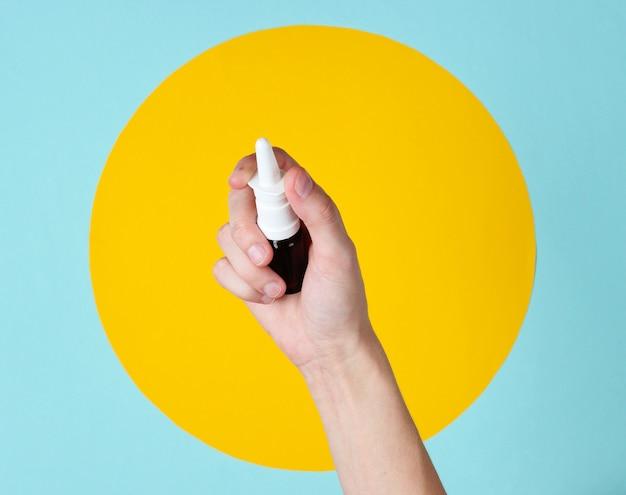 女性の手は、黄色の円で青に鼻スプレーを保持します