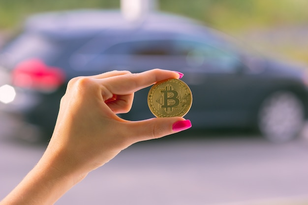 A female hand holds one bitcoin, in a blurry background a car