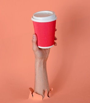 女性の手は、破れたピンクの紙を通して紙のコーヒーカップを保持します。ミニマルなコンセプト