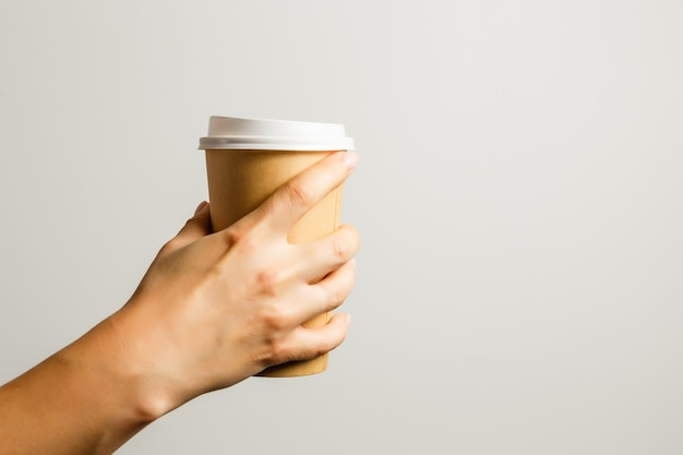 Female hand holds a paper cup with coffee on a gray background. concept of coffee, a warming drink, breakfast.