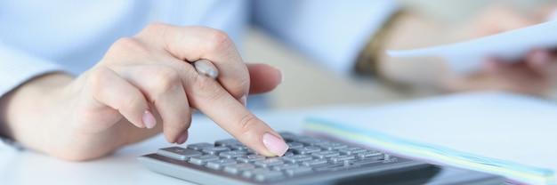 女性の手がペンを持ち、電卓の会計サービスとコンサルティングで数字を押す