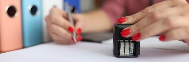 Женская рука держит ручку и печать для документов.