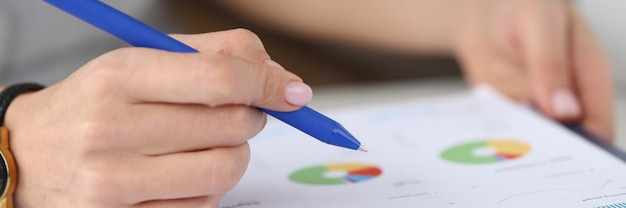 Female hand holds pen over graph with business records business reporting and development
