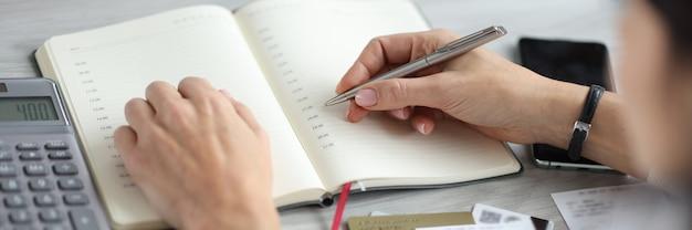 Женская рука держит ручку над дневником возле банковских карт и калькулятора планирования семейного бюджета