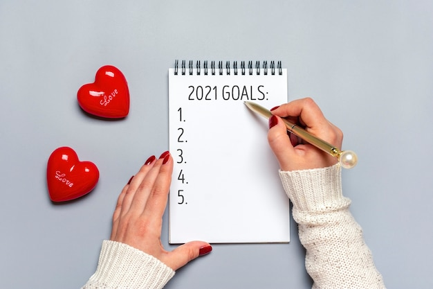 Female hand holds pen and writes 2021 new year goals on white notepad, two red hearts on gray