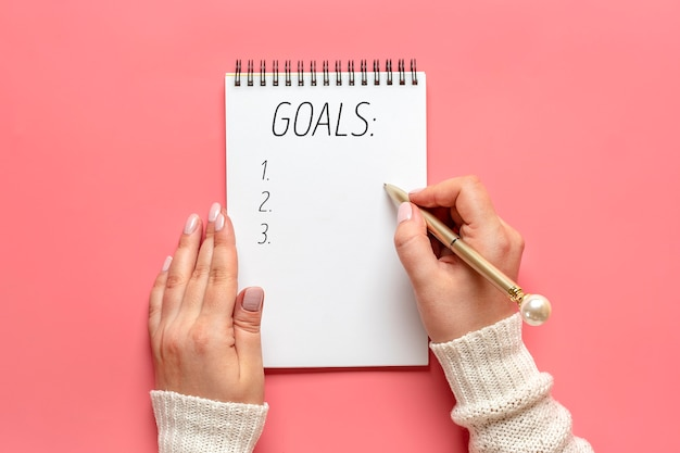 Female hand holds pen and writes new year 2021 goals on white notepad