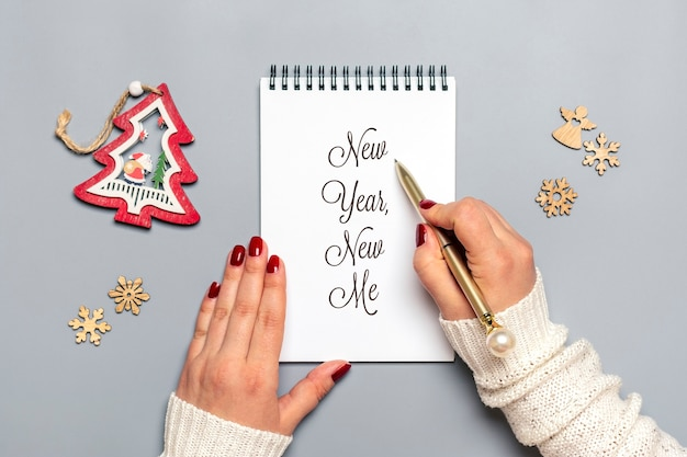Female hand holds pen and writes new year, new me on white notepad, tree, snowflake on gray