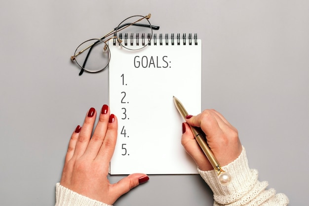 Female hand holds pen and writes text 2021 new year goals on white notepad on gray
