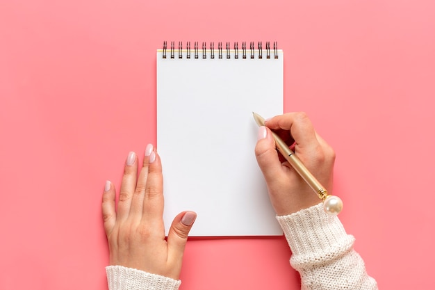 Female hand holds pen and writes on white notepad