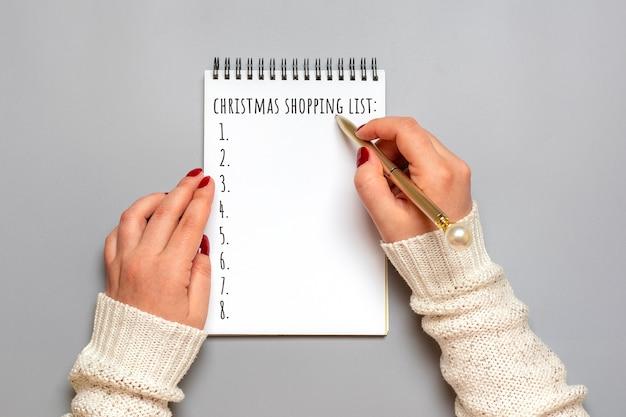 Женская рука держит ручку, пишет список покупок на рождество, идеи подарков на белом блокноте на сером
