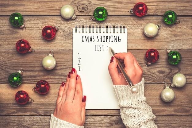 Женская рука держит ручку, пишет рождественский список покупок, идеи подарков на белом блокноте на деревянном