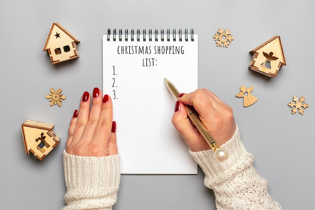 Female hand holds pen, writing christmas shopping list, gift ideas on white notepad on gray