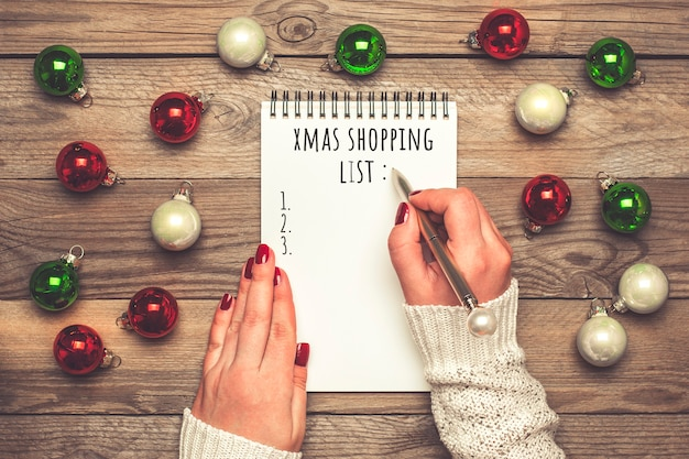Female hand holds pen, writing christmas shopping list, gift ideas on white notepad on wooden