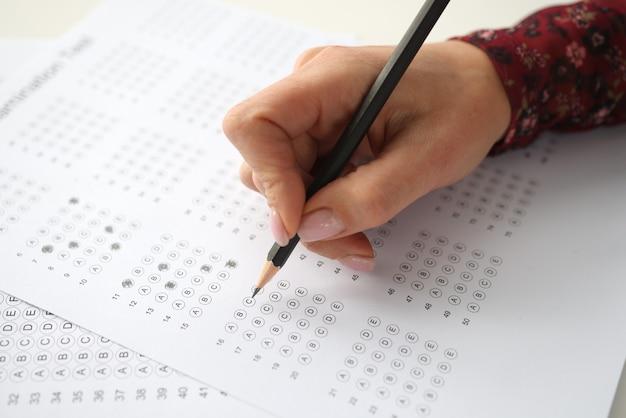 女性の手は鉛筆を持ち、テストの答えをマークします。採用テストの概念