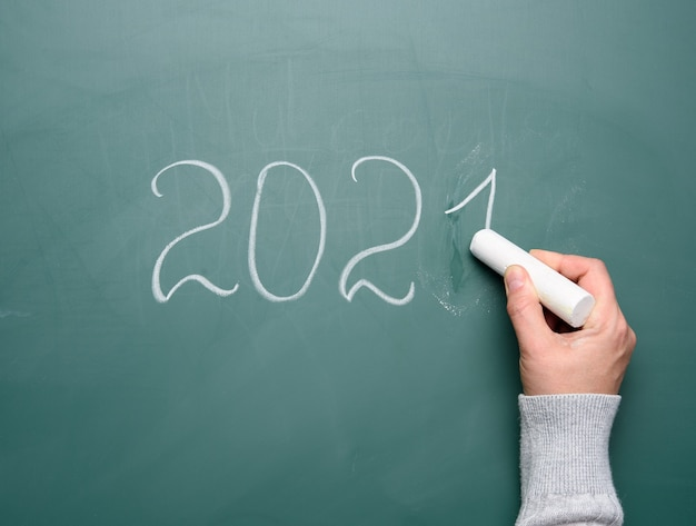Female hand holds a piece of white chalk and writes on green school board 2021, new year flat lay,
