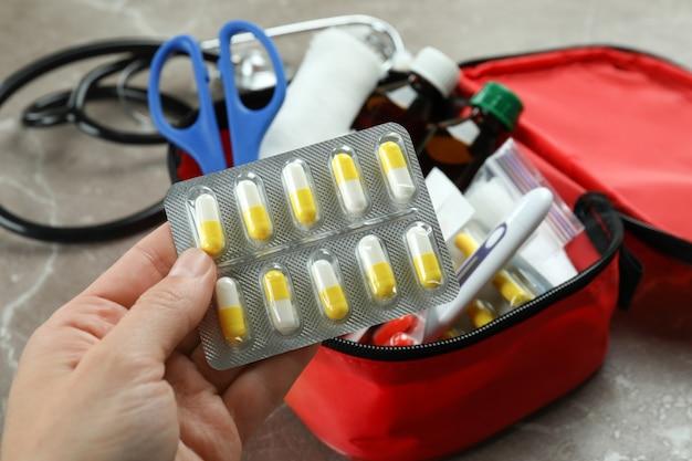 Женская рука держит таблетки и аптечку первой помощи, крупным планом