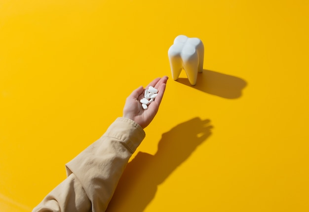 Female hand holds pills near the tooth on yellow surface
