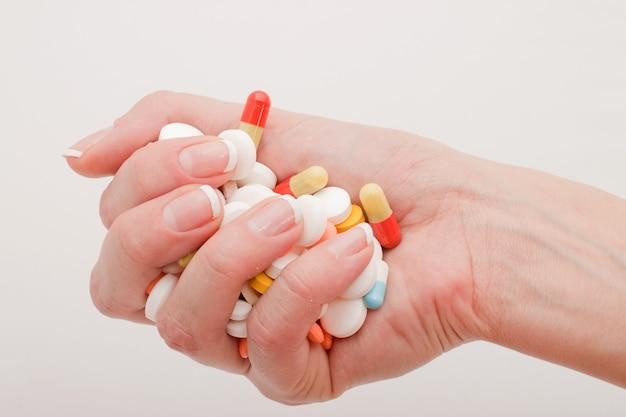 女性の手は白い背景の上の丸薬を保持します。回復と予防の治療の概念