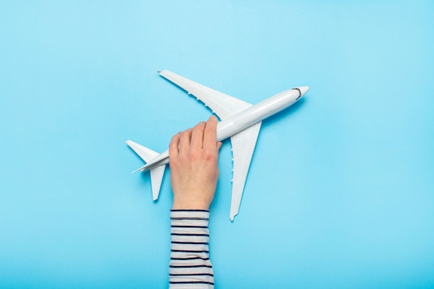 Female hand holds a plane on a blue. concept flight, tickets, booking, flight search, travel.