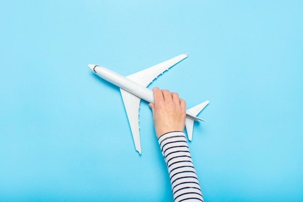 Female hand holds a plane on a blue space. concept flight, tickets, booking, flight search, travel