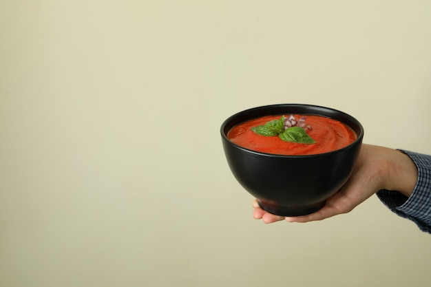 Female hand holds plate of tasty gazpacho soup