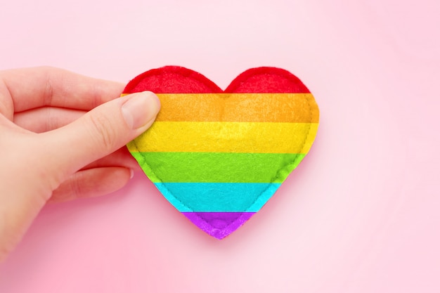 Female hand holds a rainbow heart, symbol of the lgbt community on a pink background, greeting card, background for poster, flyer, banner, copy space. lgbt background. heart shape painted in lgbt flag