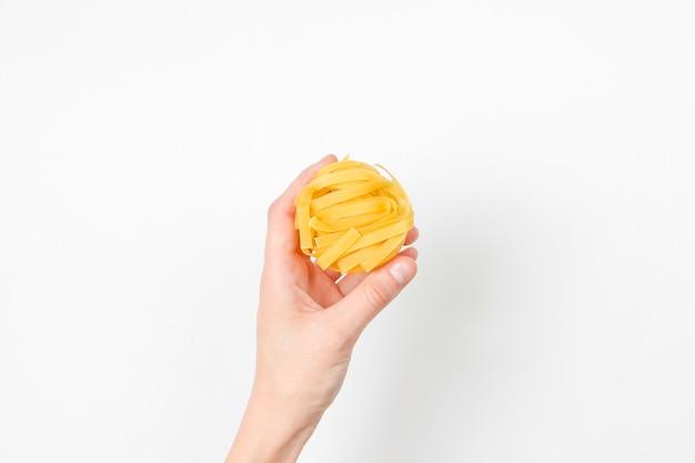 女性の手は、白の生タリアテッレ麺を保持しています。ミニマルな食品のコンセプト。上面図