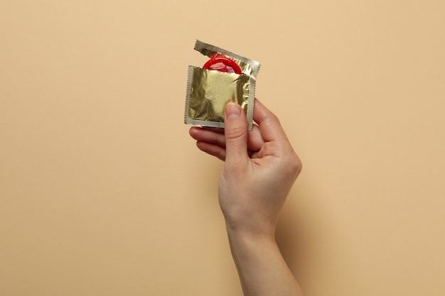 Female hand holds red condom on beige surface