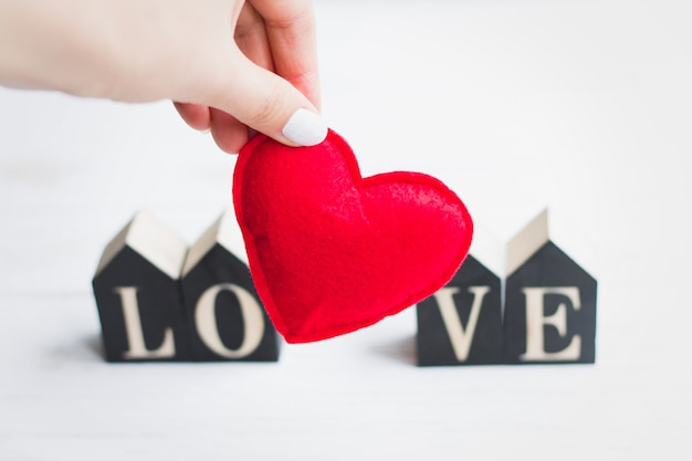 Female hand holds a red heart on the background of the word love. valentine`s card on white wooden background