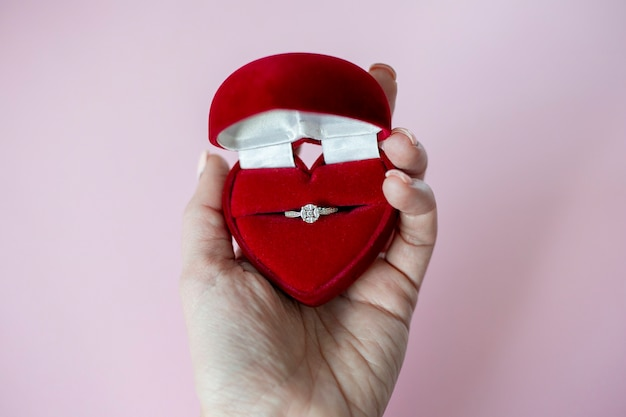 Female hand holds red heartshaped box with engagement ring on pink background