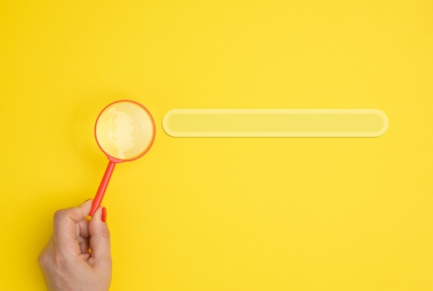 A female hand holds a red plastic magnifying glass on a yellow background, next to a line for entering and searching for information