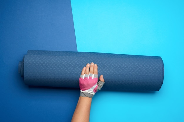 Female hand holds a rolled-up neoprene sports mat on a blue background