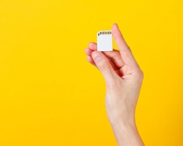 Женская рука держит карту памяти sd на желтом. минималистская техно-концепция.
