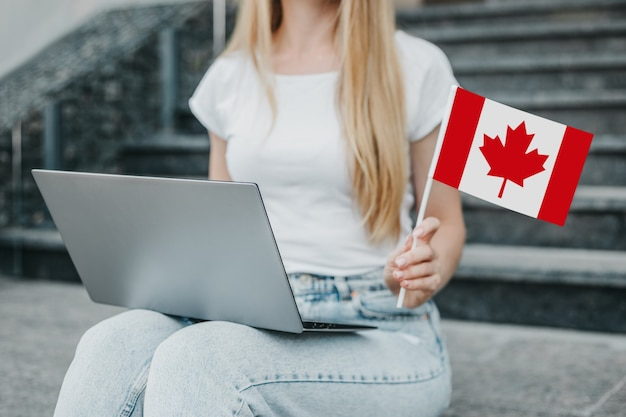 A female hand holds a small canada flag and a laptop on the background of the university. close up