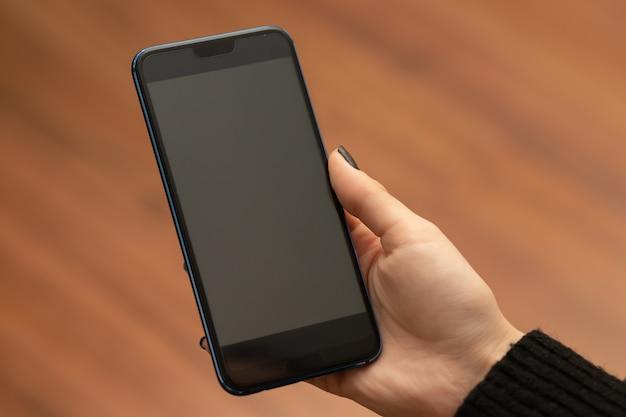 Female hand holds smartphone