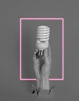 Female hand holds spiral light bulb through torn  paper with neon frame