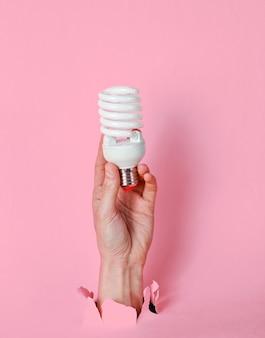 女性の手は、破れたピンクの紙を通してらせん状の電球を保持しています。ミニマルなクリエイティブなファッションコンセプト